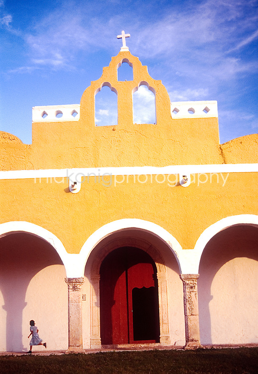 A girl runs in front of a yellow walled buliding in the yellow city of Izamal, Mexico.