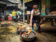 "17 AUGUST 2016 - BANGKOK, THAILAND: A woman burns ""ghost money"" in front of her home during the Ghost Festival in the Chinatown section of Bangkok. The Ghost Festival is a Buddhist and Taoist holy day celebrated on the 15th day of the 7th lunar month. It is primarily celebrated in China and Chinese communities beyond China. In Thailand, it's celebrated in Thai-Chinese communities in Bangkok, Phuket and Chiang Mai.  On that day ghosts and spirits, including those of the deceased ancestors, come out from the lower realm to visit the living. Families prepare elaborate banquets for the spirits and burn ""ghost money"" for the spirits to use in the other realm. It is a day for venerating dead relatives.     PHOTO BY JACK KURTZ"