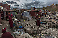 For a story by Ed Wong : CHINASICHUAN - Two journals in Sichuan<br /> Yarchen Gar, Sichuan, China<br /> October 11th, 2016<br /> A street with a collective water tap in the living quarters of Yarchen Gar a Buddhist academy where thousands of mainly nuns live and study. Wood planks have piled up to build new huts. The living and sanitary conditions in Yarchen Gar are poor with no sewage system, or running water. <br /> Gilles Sabri&eacute; for The New York Times