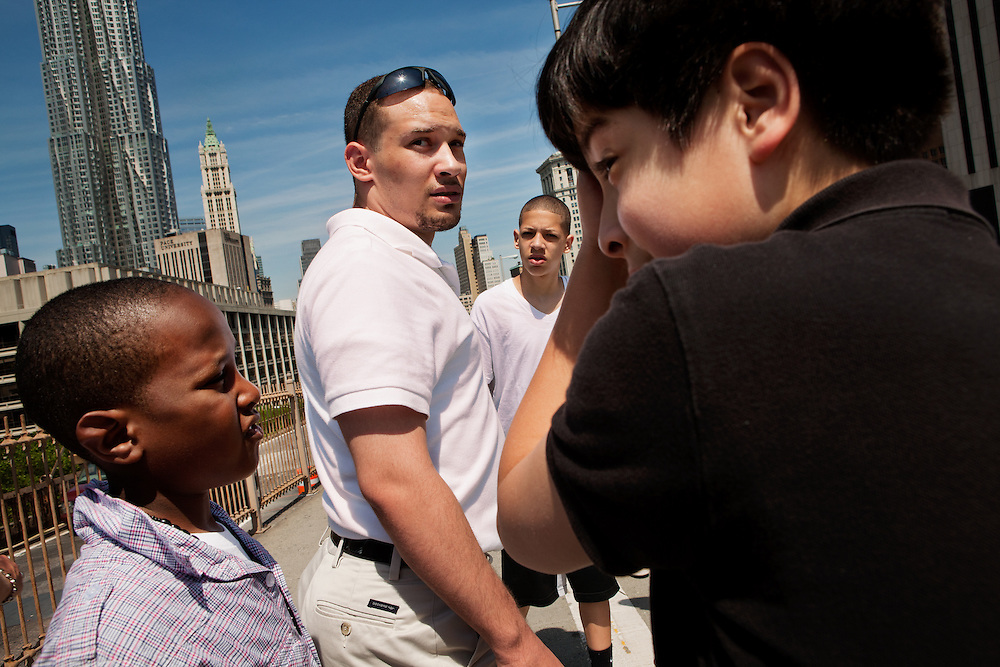 """NEW YORK, NY – MAY 25, 2011: Isaiah Brown, Sergio Alvarez and Alex Rodriguez surround twenty year-old Basilio Bonilla on a field trip to New York City. Bonilla is a volunteer with the Donegan Elemntary School and a candidate for the Bethlehem Area School Board.<br /> <br /> In 2003, the Pew Hispanic Center released a report forecasting a dramatic shift in the population of Hispanic-American youth. According to the report, the number of American-born Hispanics in U.S. schools would double by 2020, and the rate of Hispanic births in the United States would soon """"outpace"""" immigration. <br /> <br /> By 2010, schools in Eastern Pennsylvania's Lehigh Valley already embodied this fundamental shift. On May 25, 2011, children in the Leadership program at Donegan Elementary School traveled to New York City for a field trip. Walking under, over, inside and on top of America's iconic structures, the group of predominantly second and third generation Hispanic children experienced for the first time the city to which many of their families immigrated decades before. This burgeoning generation is like a bridge between cultures - the City a backdrop on which they explore their new American identity."""