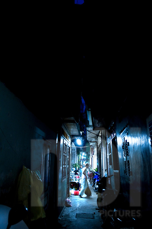 Silhouette walks at night through a very narrow alleyway, Ho Chi Minh city, Vietnam, Southeast Asia