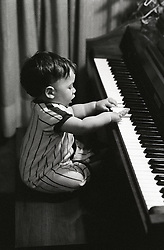baby boy playing the piano on his own