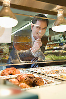 Mature man grins through glass of meat counter in supermarket