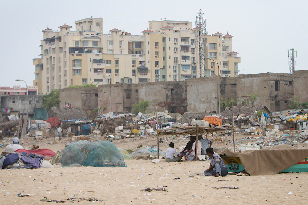 Homeless encampments on Ghandi Beach border government constructed buildings, and further back, luxury estates in Chennai, India.