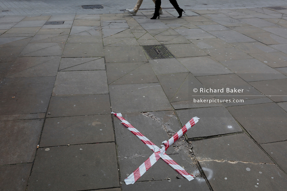 Walking legs and hazard tape stretched across a broken paving slab on a Clerkenwell Street in the borough of Islington, on 20th November 2019, in London, England.