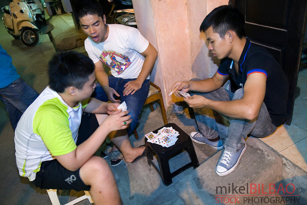 young men playing cards in the street.<br />