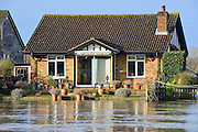© Licensed to London News Pictures. 05/01/2014. Weybridge, UK. Floodwater encroaches on gardens. Rising river levels in the River Thames at Weybridge, Surrey, threaten local housing along the river today 5th January 2014. Britain is experiencing flooding and more heavy rain is expected. Photo credit : Stephen Simpson/LNP