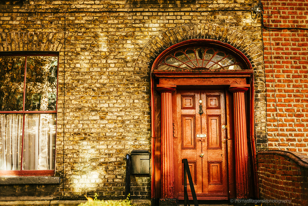 Dublin, Ireland. An old and collapsing red door on a brown brick house as the warm Autumn Sun shines dappled light on the fascade