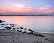 Driftwood on the beach with the Chesapeake Bay sunset in the background, Matapeake Beach, Maryland.