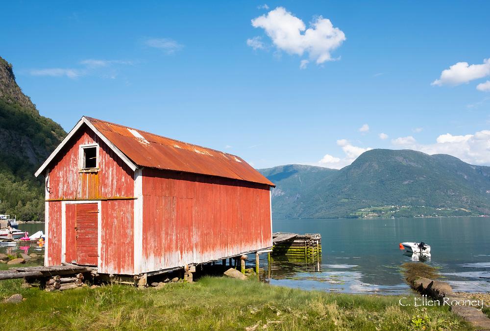 An old red wooden boathouse in Solvorn, Lustra Fjord, Vestlandet, Norway
