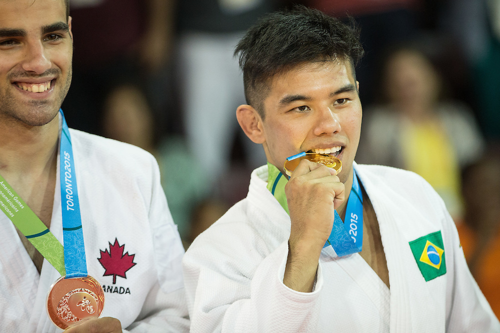 Gold medalist Marti Malloy (R) bites his medal following the medal ceremony for the men's judo 66kg class at the 2015 Pan American Games in Toronto, Canada, July 12,  2015   AFP PHOTO/GEOFF ROBINS