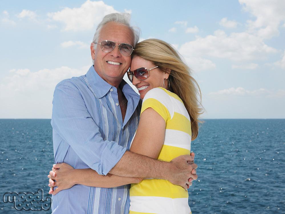 Middle-aged couple embracing against sea portrait