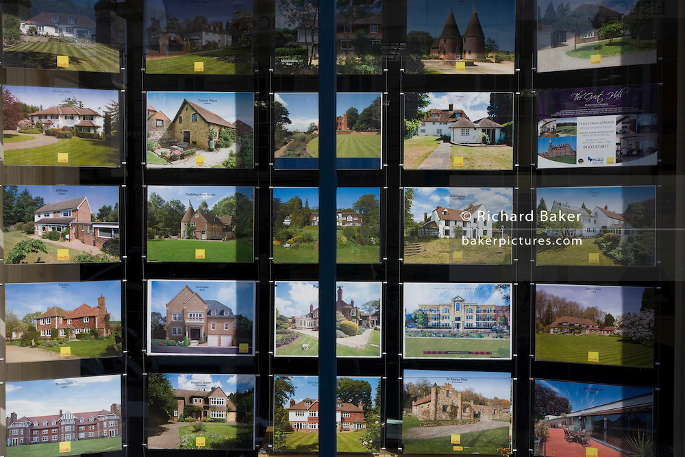 An assortment of properties are displayed in a Sevenoaks estate agent's high street window.