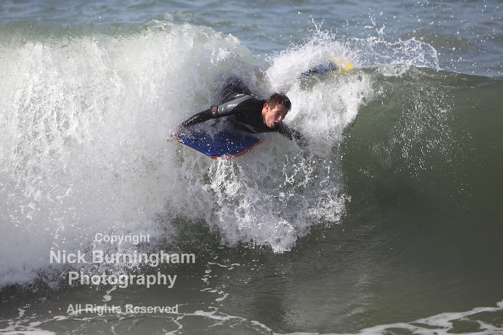 NEWQUAY, CORNWALL, UK - AUGUST 10: The remnants of Hurricane Bertha hit the Cornish coast causing rough seas and high surf. Young and old enjoy the unusually high seas.