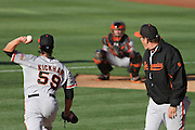 OAKLAND, CA - MAY 28: Mike Kickham (59) warms up with Buster Posey (28) before his Major League debut against the Oakland Athletics under the watchful eye of San Francisco Giants pitching coach Dave Righetti.