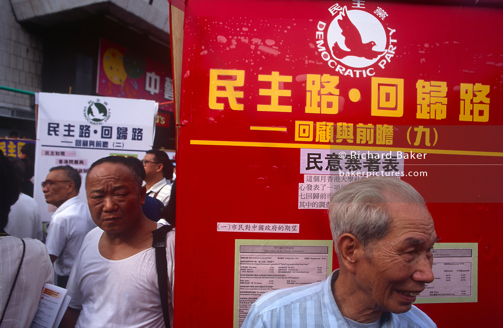 Chinese activist gentlemen and a sign for the Democratic Party of Hong Kong the day after the Handover of sovereignty from Britain to China, on 30th June 1997, in Hong Kong, China. Midnight signified the end of British rule, and the transfer of legal and financial authority back to China. Hong Kong was once known as 'fragrant harbour' (or Heung Keung) because of the smell of transported sandal wood.