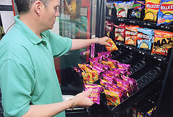Man with disability filling vending machine in leisure centre,