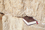 Israel, Jerusalem, Old City, Wailing Wall close up of the request notes stashed into the cracks  between the large stones and a Jewish prayer book (Sidur) By tradition, these notes are read by God