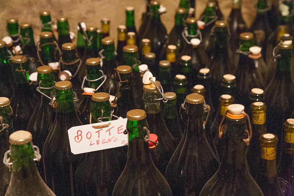 bottles of wine from craft vintner in northern Italian wine cellar, Village of Mongardino near Asti