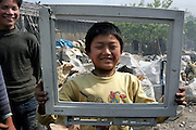 "A migrant child from Henan province holds up a piece of e-trash, once a computer screen bearing a ""Nokia"" logo in a junk yard in Guiyu in Guangzhou province."