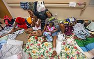 Bresil Rosemonde, of Haiti, seeks shelter with her children, left to right, Monica , 19, Nekeisha, 9 and Jasmine Baptist, 4, at the Marsh Harbour Health Center in Abaco, Bahamas on Wednesday, September 4, 2019