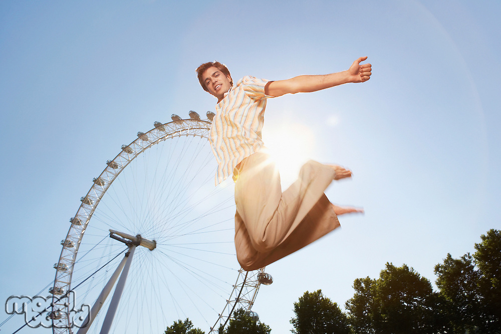 Young man in park jumping in front of London Eye portrait low angle view