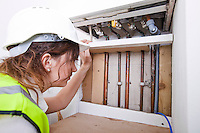 Female plumber examining pipes of central heating boiler