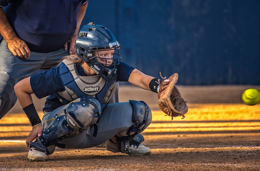 Catcher accepts ball in softball game