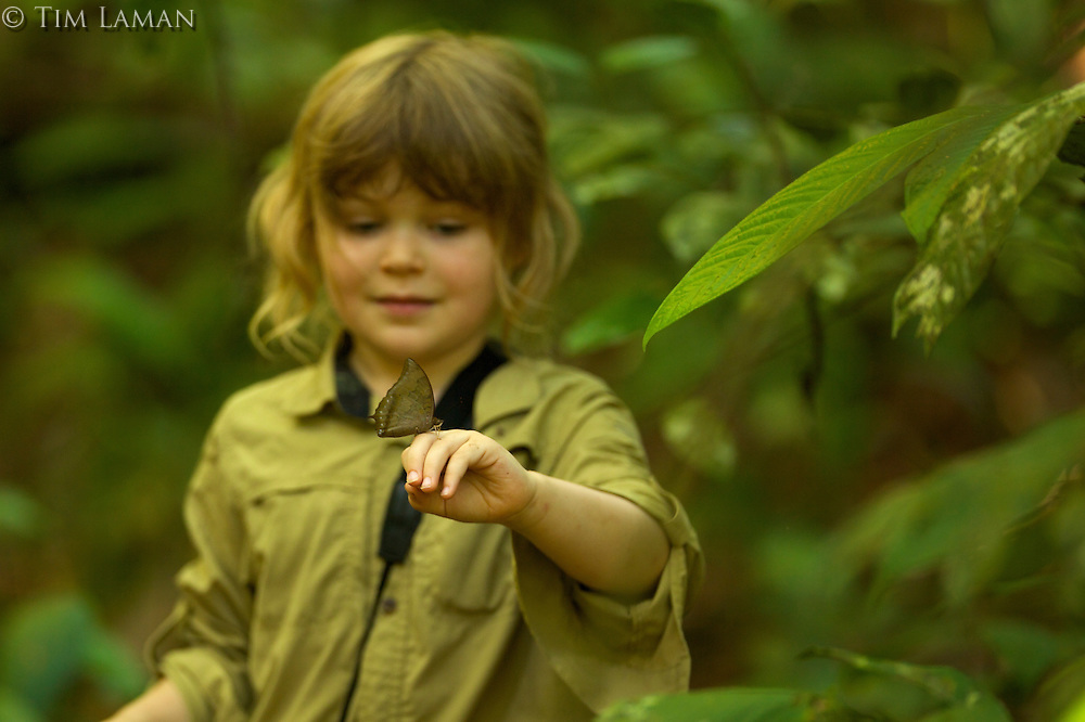A gril holding a butterfly on her hand in the rain forest in Borneo.