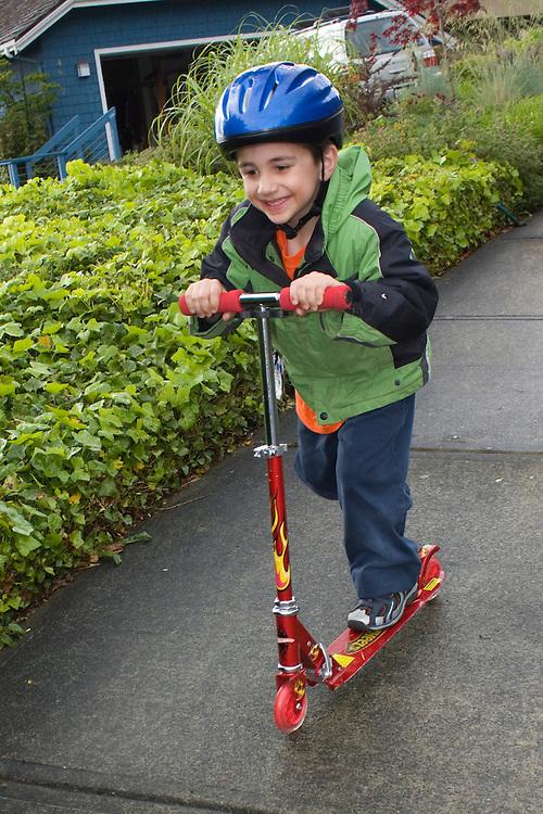 United States, Washington, Bellevue, boy (age 6) on scooter.  MR, PR