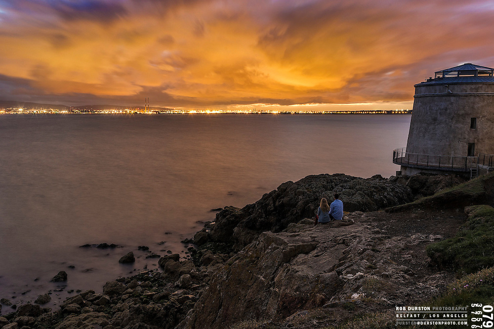 Couple at the Martello Tower at sunset in Sutton, Dublin