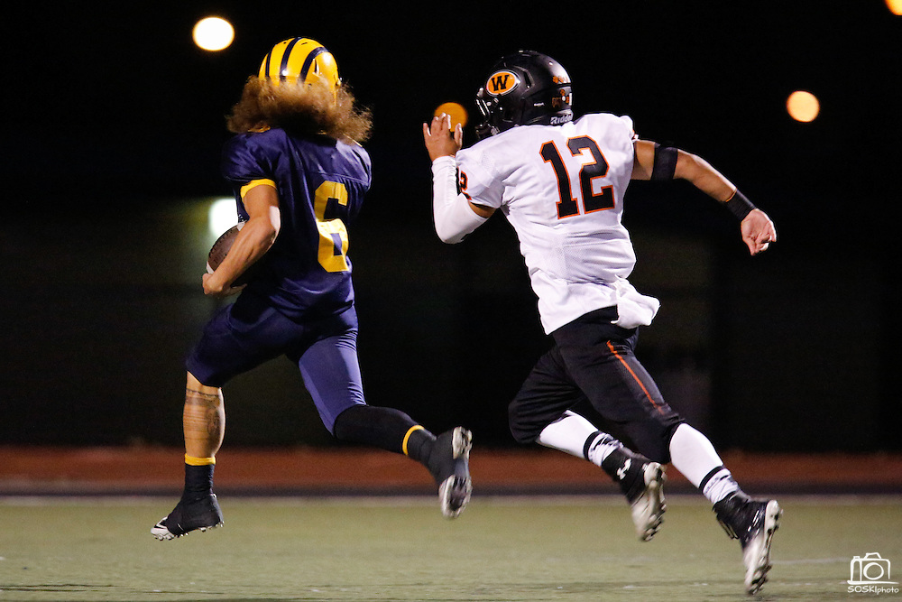 Milpitas High School running back Dylan Slack (6) beats Woodside defensive back Tommy Cook (12) down the field at Milpitas High School in Milpitas, California, on September 13, 2013. The Trojans went on to beat the Wildcats 50-6. (Stan Olszewski/SOSKIphoto)