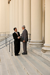 Two men shaking hands on courthouse steps