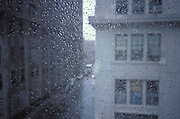 view of loft buildings through rainy window