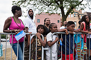 Cousins Dayonna, 7, and Malik, 10, center, watch as the Kenwood Academy Marching Band passes by at the Bud Billiken Parade on August 12, 2017.