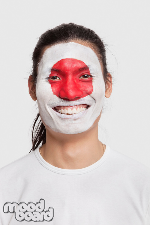 Portrait of happy young mixed race man with Japanese flag painted on face against white background