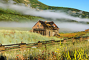 A low morning cloud layer passes near an abandoned log cabin. Hwy 135 near Crested Butte.