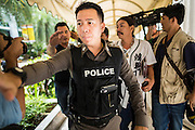 "31 MAY 2014 - BANGKOK, THAILAND: Thai police push through a crowd as they lead away a young man they detained after he walked down a sidewalk holding a sign that said ""Respect my vote"" in a solitary protest against the military government. Bangkok was mostly quiet Saturday. There were only a few isolated protests against the coup and military government.    PHOTO BY JACK KURTZ"