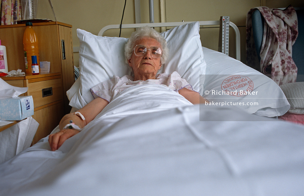 Elderly lady patient recovering in bed in the surgical ward of the Royal London Hospital Whitechapel