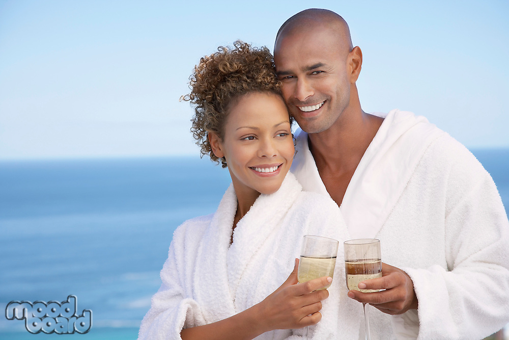 Couple in bathrobes holding drinks embracing ocean in background half length
