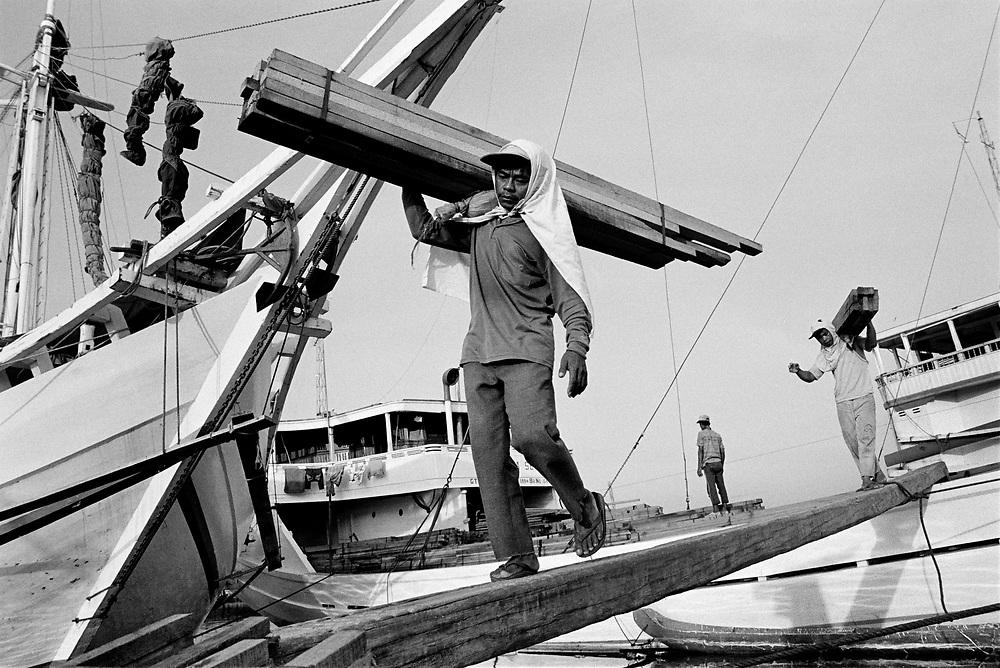 Exotic timber is unloaded from wodden shipes called 'Pinisi' at the port of Sunda Kelapa in Jakarta, Indonesia