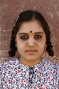 Teenage girl with braids and ring in her nose at Hindu Rat Temple in Deshnoke, Rajasthan, India. The ornate Hindu temple was constructed by Maharaja Ganga Singh in the early 1900s as a tribute to the rat goddess, Karni Mata.