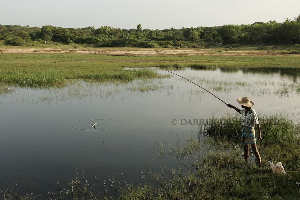 A fisherman fishes in a small lake outside Hambantota, Sri Lanka, on January 16, 2005..Photo by Darrin Zammit Lupi