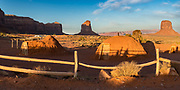 Gray Whiskers Butte, Mitchell Butte, and Hogan Village at sunrise in Monument Valley Navajo Tribal Park, Arizona, USA. This image was stitched from multiple overlapping photos.