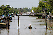 Mekong Delta. Motorbikes on a bridge across a river arm, a traditional rowing boat passing underneath.