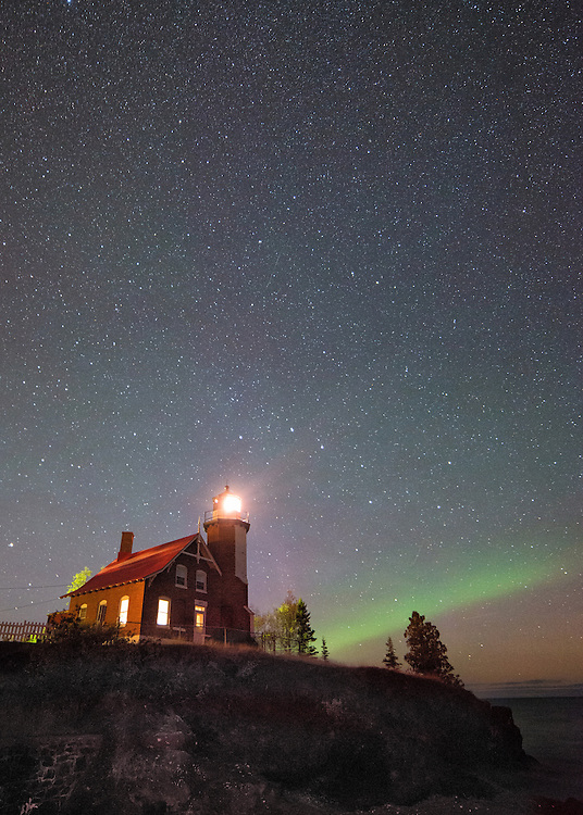 Eagle Harbor Lighthouse shines in the night sky as the Aurora Borealis forms on the horizon.