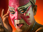 "26 NOVEMBER 2014 - BANGKOK, THAILAND: A performer puts on his makeup before a Chinese opera performance at the Chow Su Kong Shrine in the Talat Noi neighborhood of Bangkok. Chinese opera was once very popular in Thailand, where it is called ""Ngiew."" It is usually performed in the Teochew language. Millions of Chinese emigrated to Thailand (then Siam) in the 18th and 19th centuries and brought their culture with them. Recently the popularity of ngiew has faded as people turn to performances of opera on DVD or movies. There are about 30 Chinese opera troupes left in Bangkok and its environs. They are especially busy during Chinese New Year and Chinese holidays when they travel from Chinese temple to Chinese temple performing on stages they put up in streets near the temple, sometimes sleeping on hammocks they sling under their stage.      PHOTO BY JACK KURTZ"