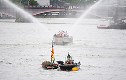 © Licensed to London News Pictures. 22/06/2016. London, UK.  A London Fire Brigade fireboat seen firing it's water hoses behine a floral tribute boat for the late Jo Cox MP, ahead of a memorial service for the Labour MP who was killed in an attack outside her constituency office. Jo Cox would have turned 42 today.   Photo credit: Ben Cawthra/LNP