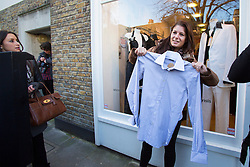 © licensed to London News Pictures. London, UK 22/11/2013. A woman celebrating after buying a shirt donated by Victoria Beckham to help raise money for Philippine typhoon disaster at the British Red Cross branch in Chelsea, London. Photo credit: Tolga Akmen/LNP