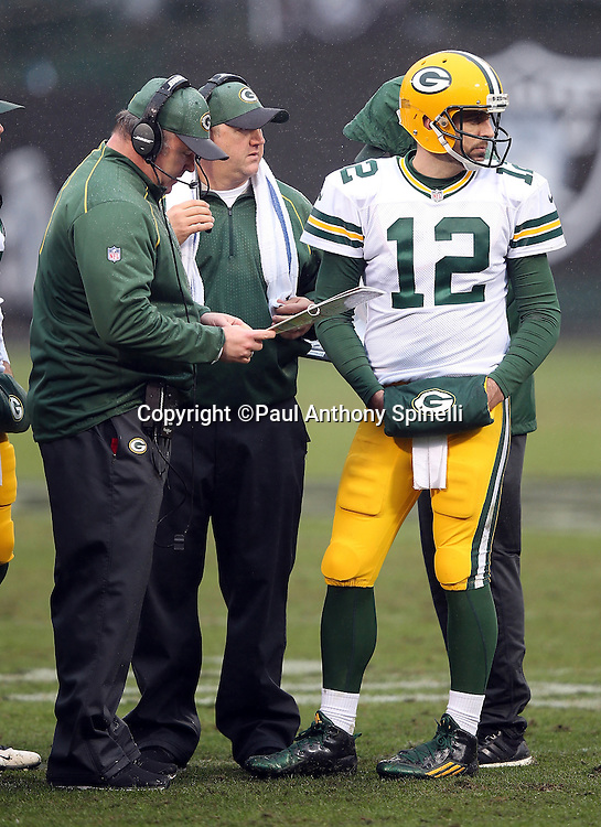 Green Bay Packers quarterback Aaron Rodgers (12) looks toward the field during a sideline conversation with Green Bay Packers head coach Mike McCarthy during the 2015 week 15 regular season NFL football game against the Oakland Raiders on Sunday, Dec. 20, 2015 in Oakland, Calif. The Packers won the game 30-20. (©Paul Anthony Spinelli)